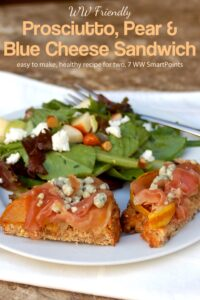Prosciutto, pear and blue cheese open-face sandwich on white plate with mixed greens salad.