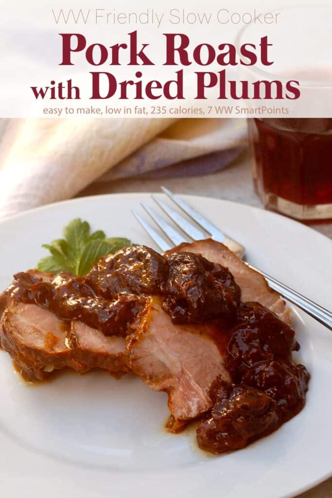 Slices of pork roast with dried plums on white dinner plate near glass of red wine.