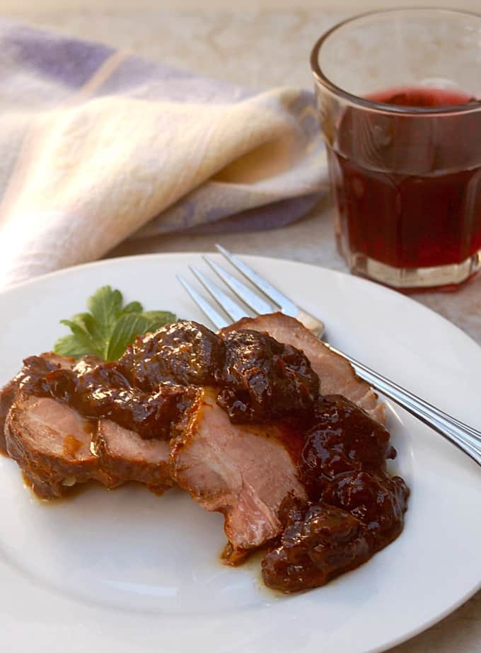 Slices of pork roast with dried plums on a white dinner plate near glass of red wine.