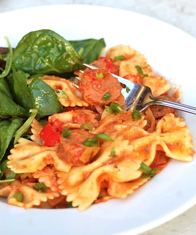 Crock pot cajun sausage pasta sauce with bow-tie pasta and fresh spinach.