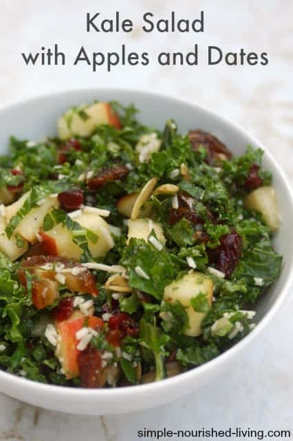 Kale salad with chopped apple and dates in white deep bowl from above