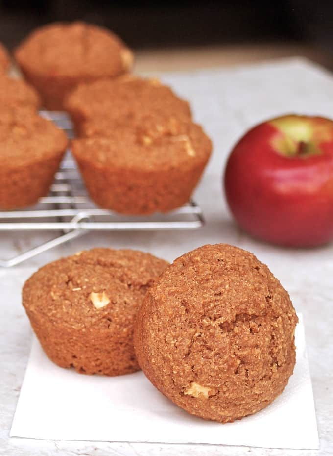 Two apple bran muffins on white napkin up close with more muffins on cooling rack and a fresh red apple in the background.