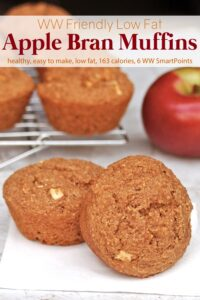 Two apple bran muffins on white napkin with more muffins on cooling rack in the background with a fresh red apple.
