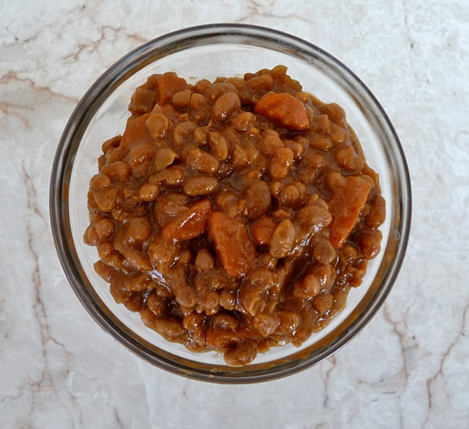 Moroccan Spiced Baked Beans in a glass bowl with a white background from above