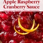 Slow cooker apple raspberry cranberry sauce with fresh orange peel up close.