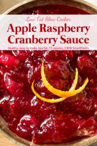 Slow cooker apple raspberry cranberry sauce with fresh orange peel up close.