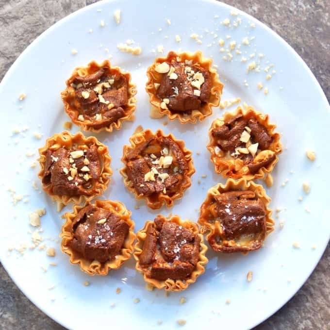 Snickers mini tarts on white plate topped with chopped peanuts.