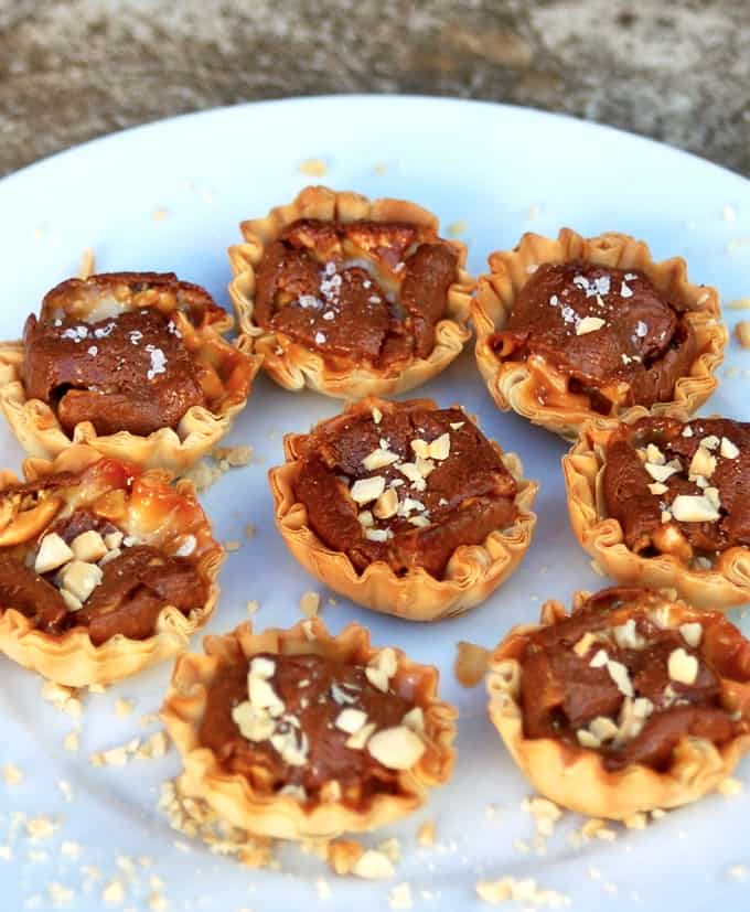 Snickers mini tarts garnished with chopped peanuts.