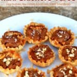 Mini Snickers tarts topped with chopped peanuts on a white plate.
