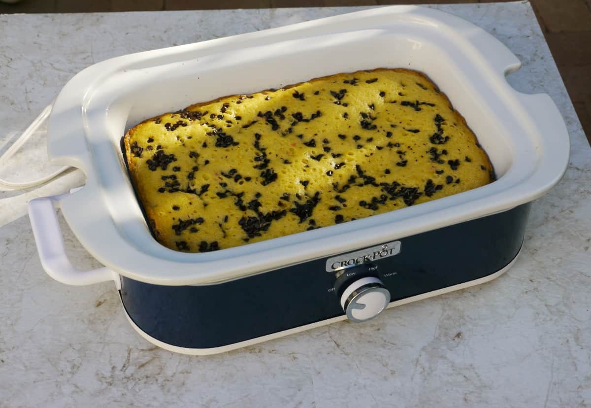 Fruit Cocktail Cake in blue Casserole Crock Pot on white counter.