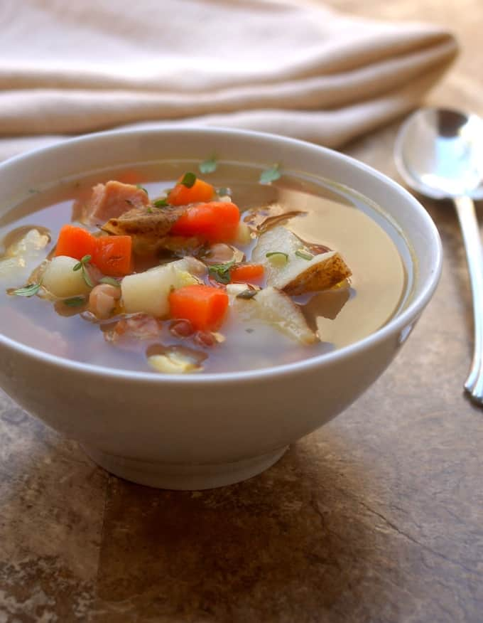 Ham bone soup with potatoes and carrots in a bowl with spoon and napkin