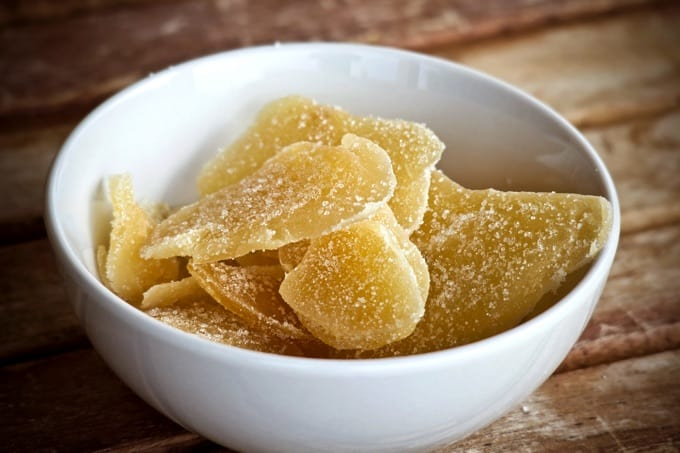 Crystallized Candied Ginger in a white bowl on a wood table