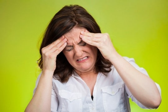 Stressed Out Woman holding her head wearing white blouse, green background