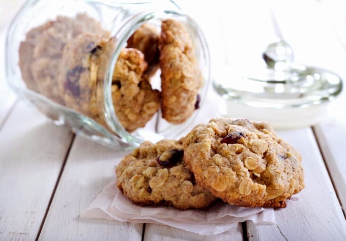 Cranberry Oatmeal Ginger Cookies in a glass cookie jar with 2 cookies in front on a napkin