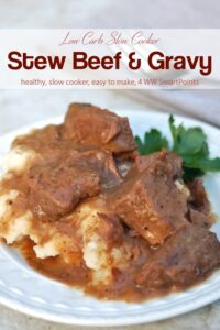 Stew beef with gravy over mashed potatoes on dinner plate