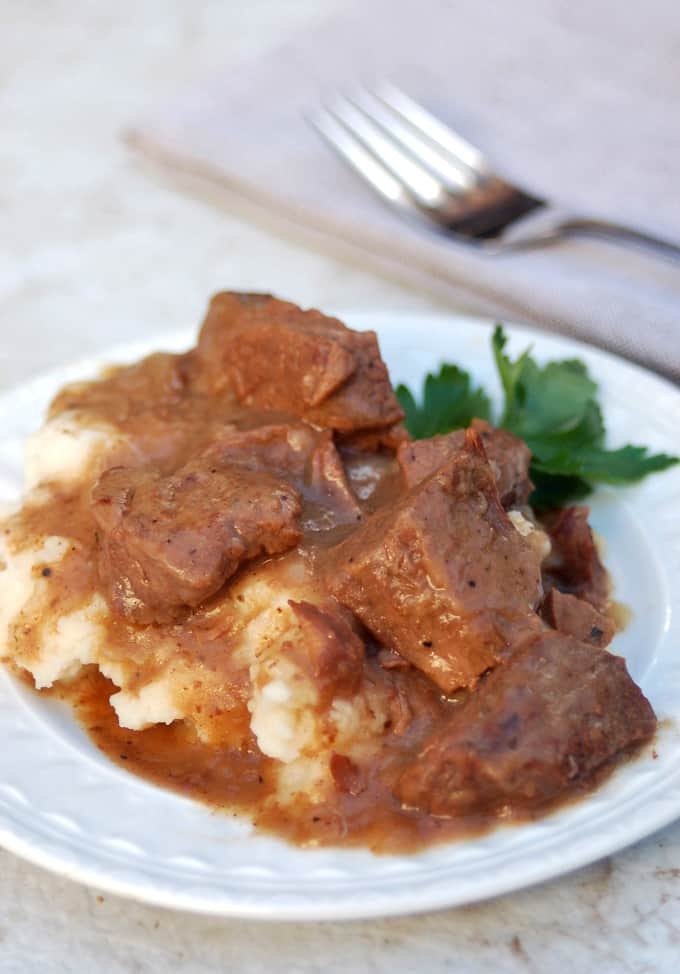 Stew beef and gravy over mashed potatoes on dinner plate