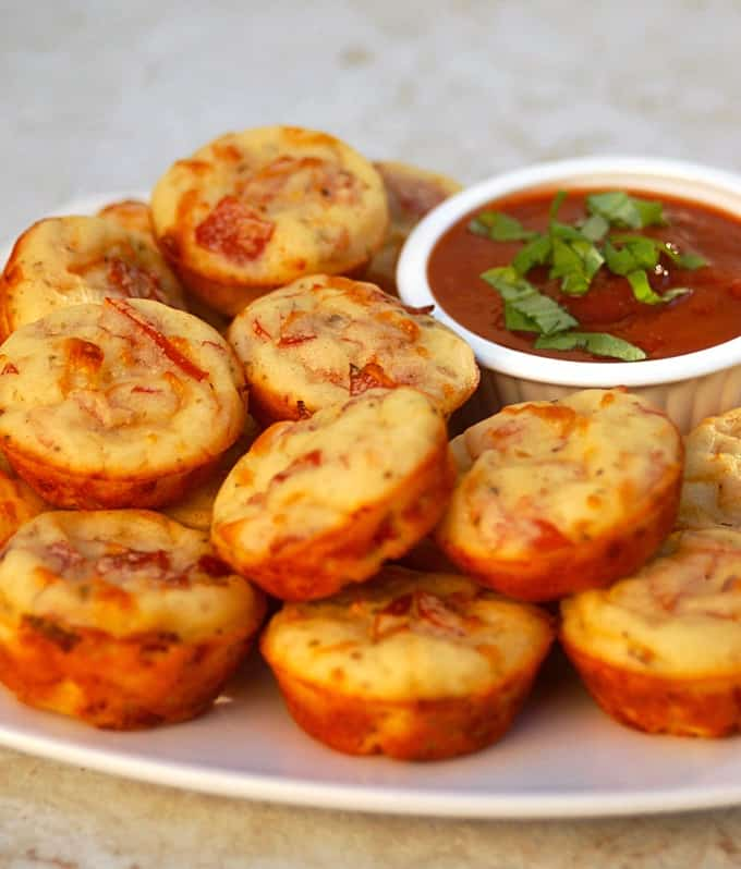 Pepperoni pizza mini muffins on serving plate with marinara dipping sauce.