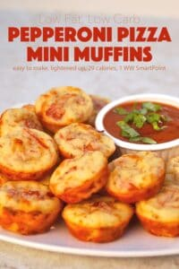 Pepperoni pizza mini muffins on white serving platter with marinara dipping sauce.