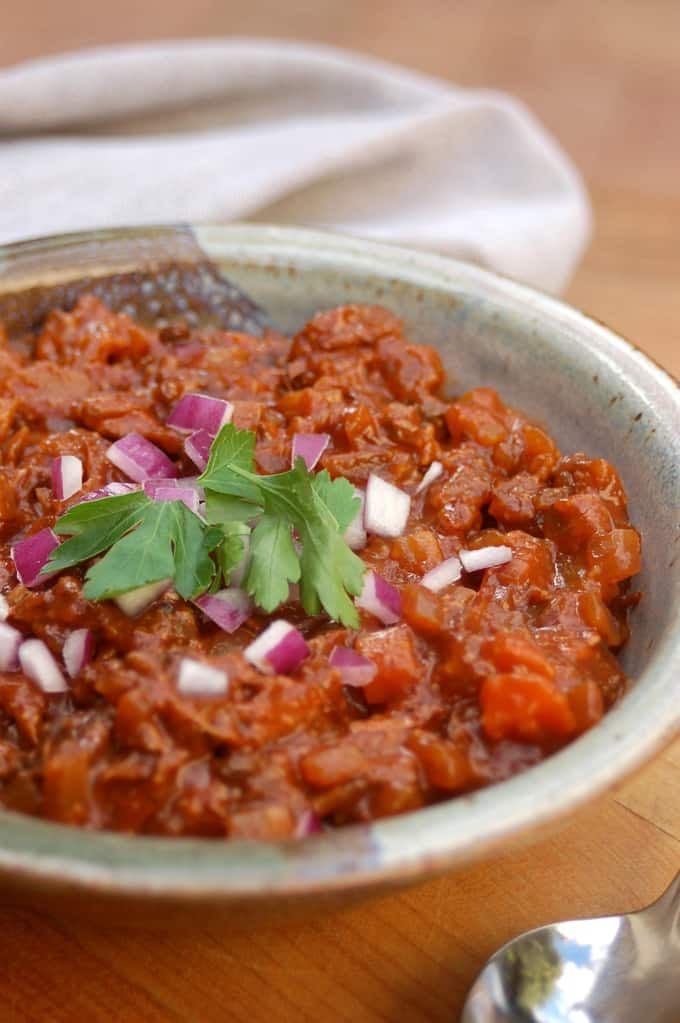 Chuck Wagon Chili without beans in a ceramic bowl topped with chopped red onion and cilantro