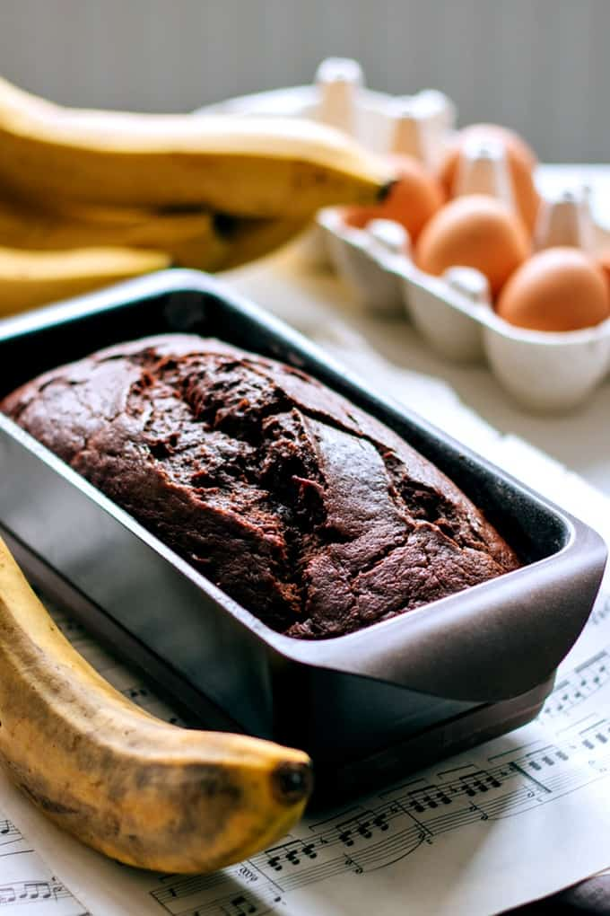 Fresh baked Chocolate Banana Bread in a baking pan with ripe bananas and a carton of eggs