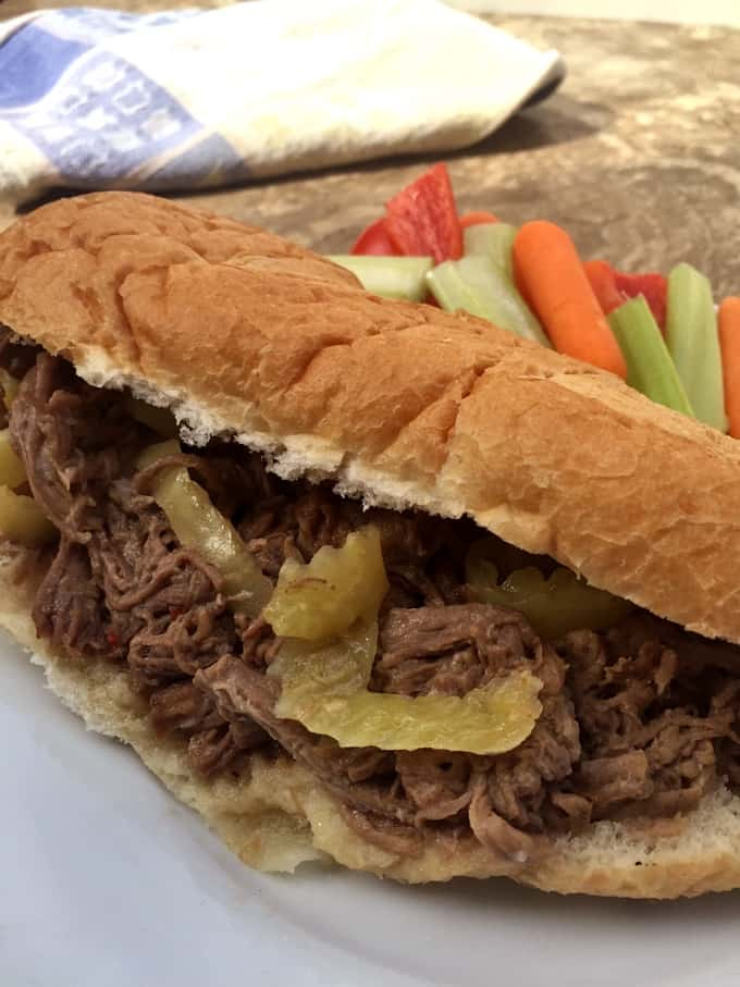 Shredded beef with Italian Pepperoncini (mild pepper rings) on a sandwich roll with vegetable sticks
