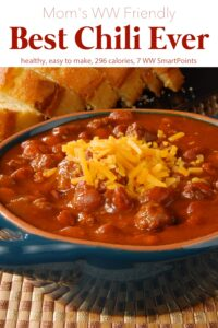 Bowl of chili topped with shredded cheese and sliced cornbread in the background.