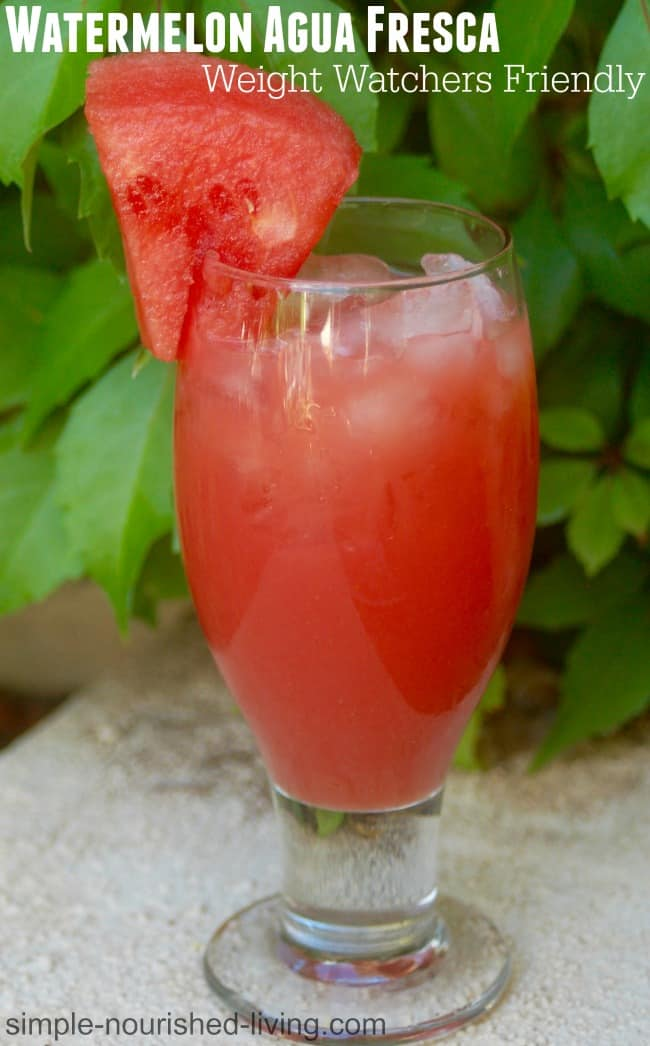 Watermelon Agua Fresca in tall glass with watermelon wedge behind green plant