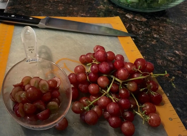 red grapes and sliced red grapes in measuring cup on counter
