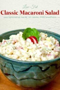 Classic macaroni pasta salad in green ceramic bowl on wood table.