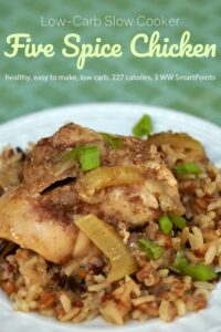 Slow cooker five spice chicken over wild rice on white dinner plate.