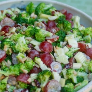 skinny broccoli salad in a ceramic bowl with green background