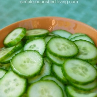 slices of english cucumber in a wooden bowl on aqua background