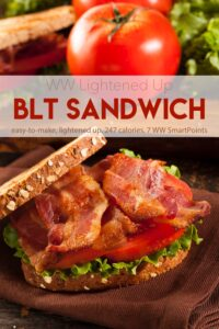 BLT sandwich on brown napkin with whole tomato and second BLT in background.