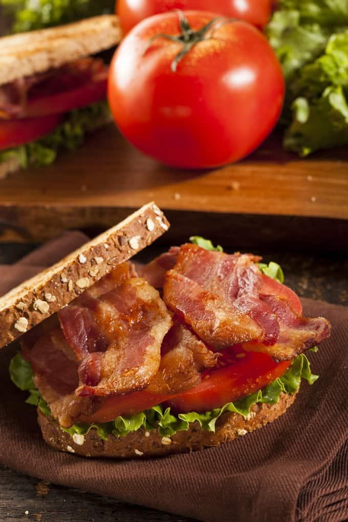 BLT sandwich on brown napkin with whole tomato and second BLT in the background.