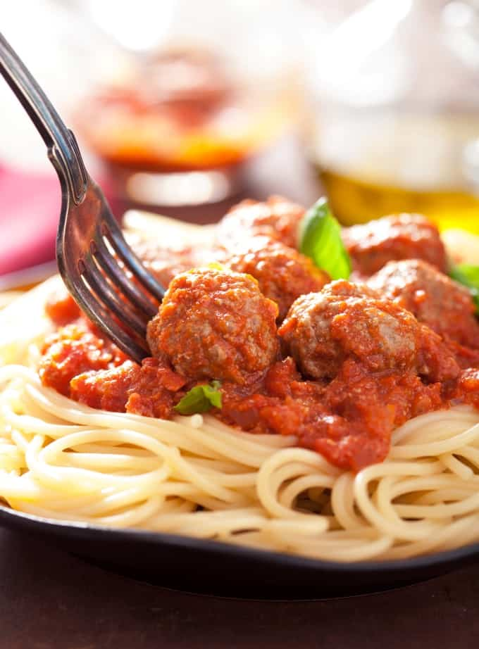 Plate of spaghetti and chicken meatballs in tomato sauce with a fork.