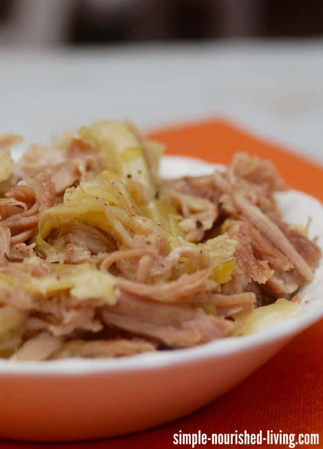 Slow cooker shredded kalua pork and cabbage in white bowl up close.