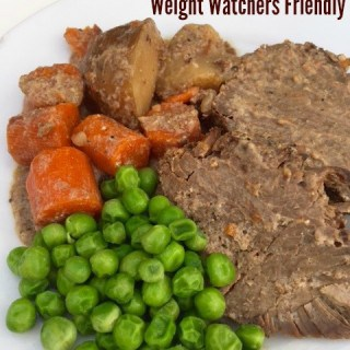 Weight pot roast with potatoes, carrots, peas on plate close up