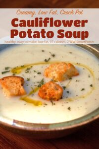 Creamy cauliflower potato soup in ceramic bowl garnished with toasted croutons, chopped herbs and olive oil drizzle.