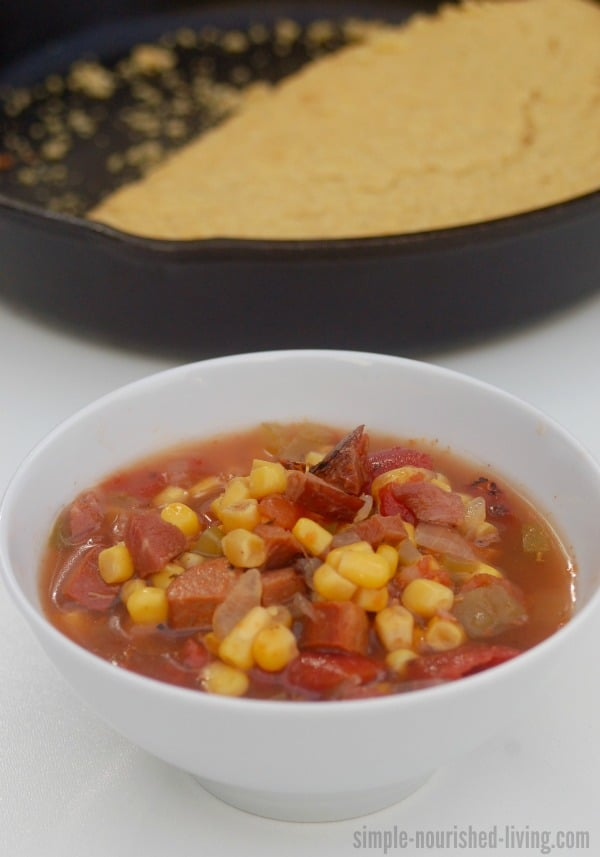 Spicy cajun soup in a white bowl with skillet cornbread in the background.