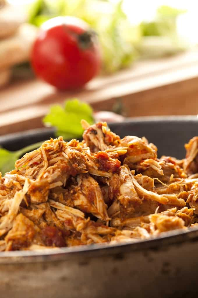Shredded chicken with salsa in a pan up close with a tomato in the background