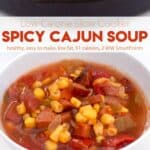 Spicy cajun soup in white bowl next to skillet cornbread.