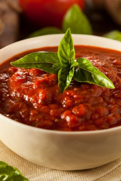 Spaghetti Sauce topped with fresh basil in small white bowl.