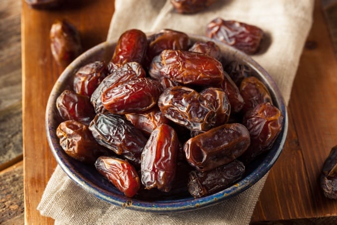 A bowl of raw, organic Medjool dates on a linen napkin on a wood table