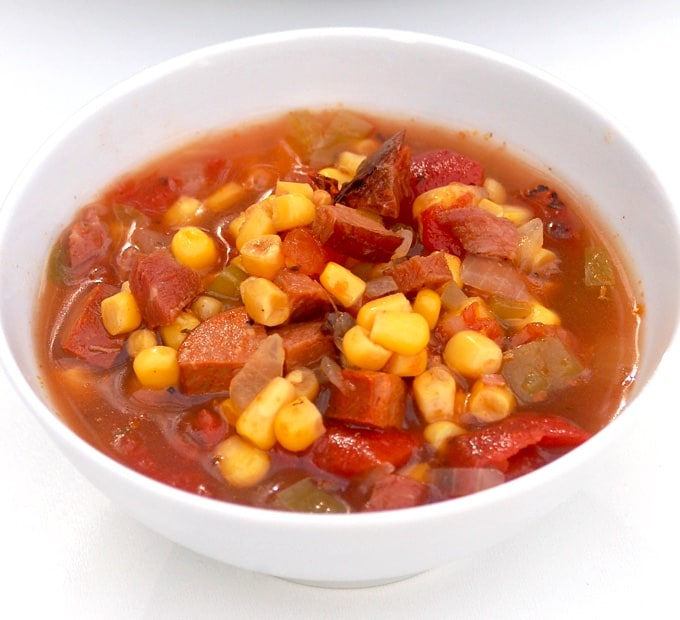 Spicy cajun soup with chicken andouille sausage and corn in white bowl.