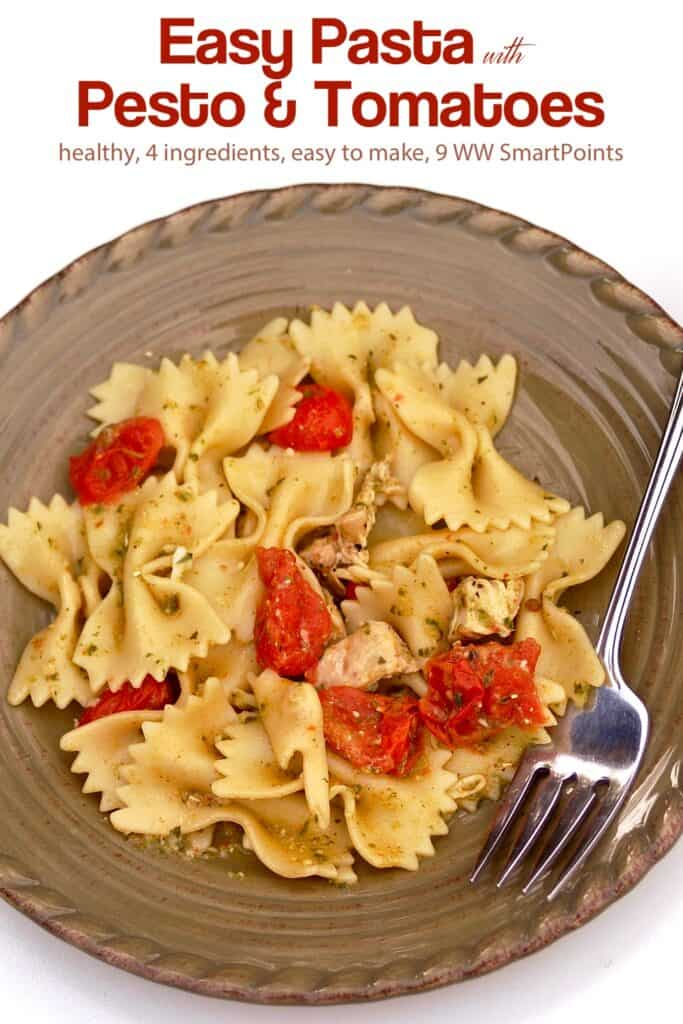 Bowtie pasta with pesto, tomatoes and chicken on dinner plate with fork