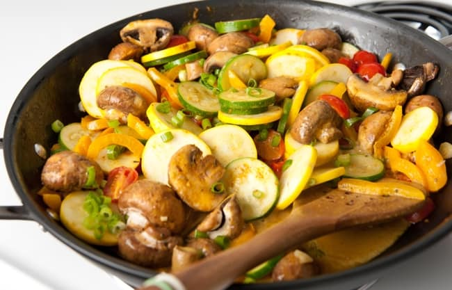 Cooking mushrooms, zucchini, yellow squash, and tomatoes in a wok on the stove
