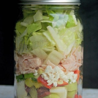 Greek Turkey Feta Salad in a Jar from side black background