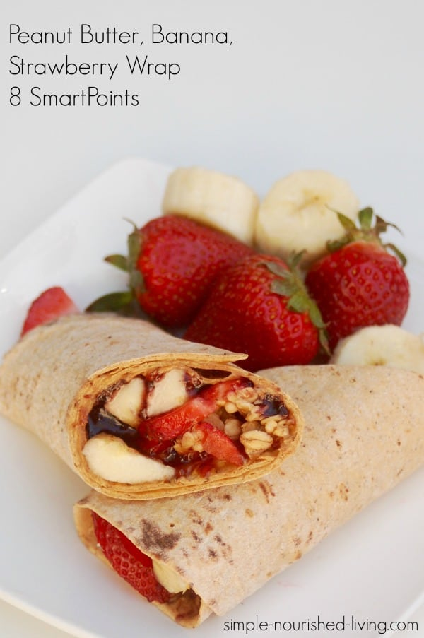 peanut butter strawberry flatout wrap halves crossed on a plate with strawberry banana garnish