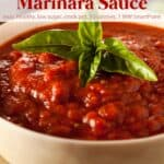 Marinara sauce garnished with fresh basil in white bowl.