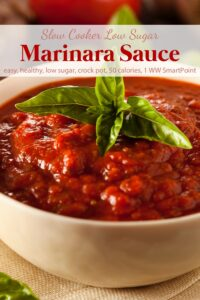 Marinara sauce garnished with fresh basil in white bowl.